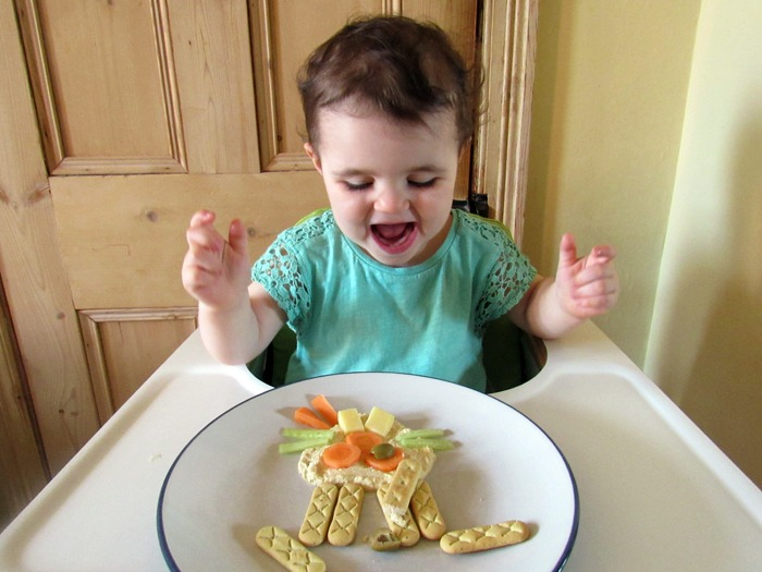A happy toddler with her lunch arranged into the face of a rabbit. A true moment of snackspiration!