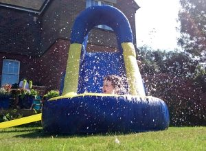 A small boy making a splash in an inflatable water slide.