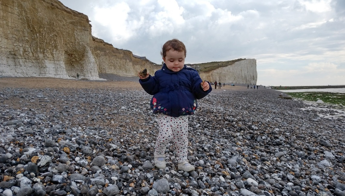 Game of Stones? A toddler on a stony beach with cliffs behind her.