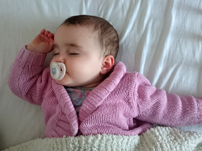 A sleeping baby who looks as though she is dreaming.