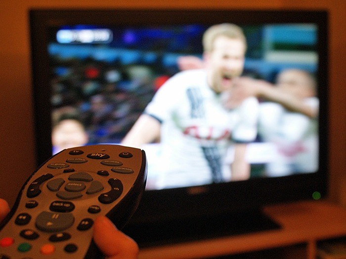 A child's hand holding a remote control with a team celebrating a goal on the television in the background.