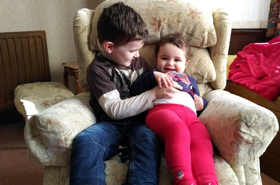 Two young children tickling each other.