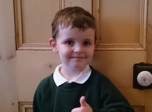 A school boy giving a thumbs up on his first day.