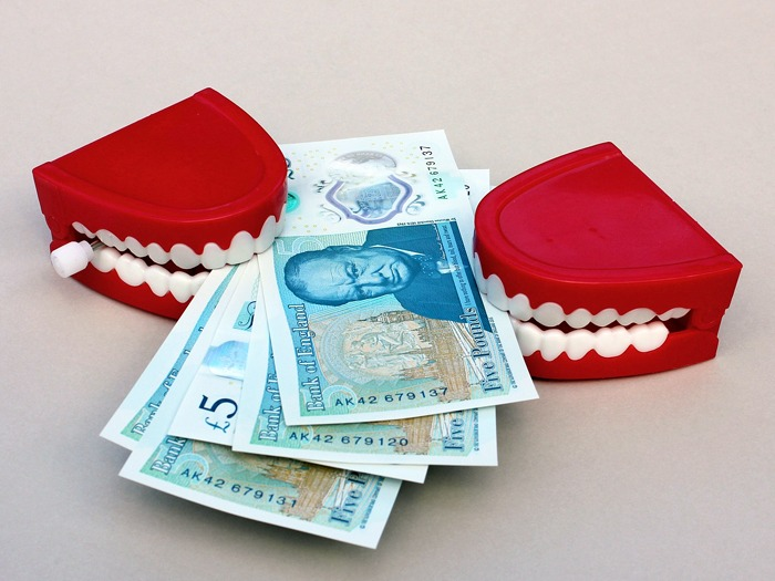 Two sets of toy chattering teeth holding a bunch of five pound notes.