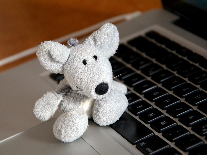 A toy mouse on a computer keyboard.