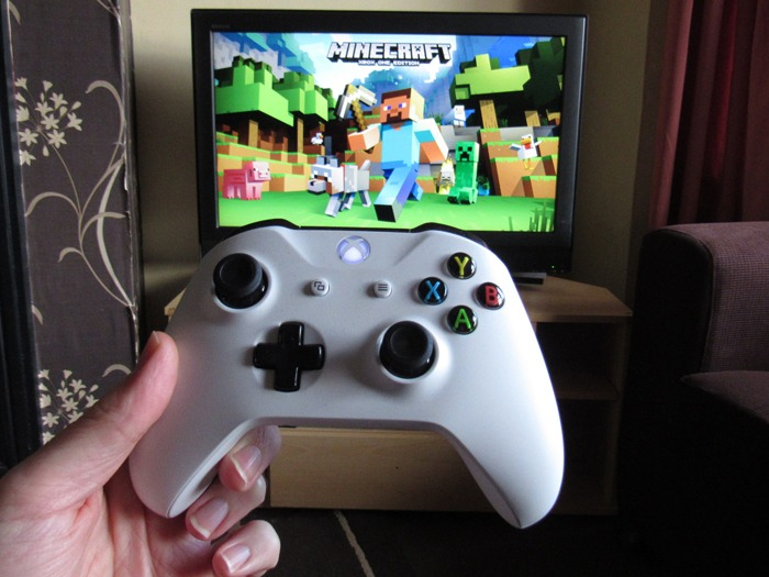 An Xbox One S controller in front of the Minecraft launch screen.