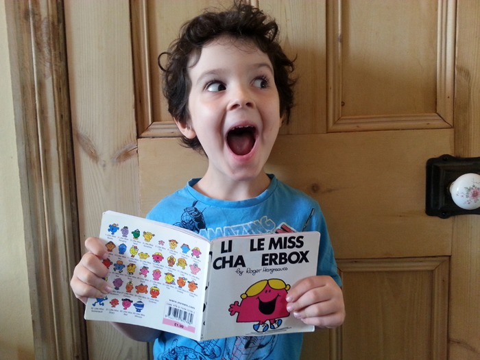 A young boy with a copy of Little Miss Chatterbox. All of the letter Ts have been removed from the photo.