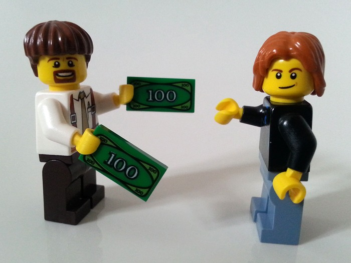 A Lego man giving money to another Lego man.