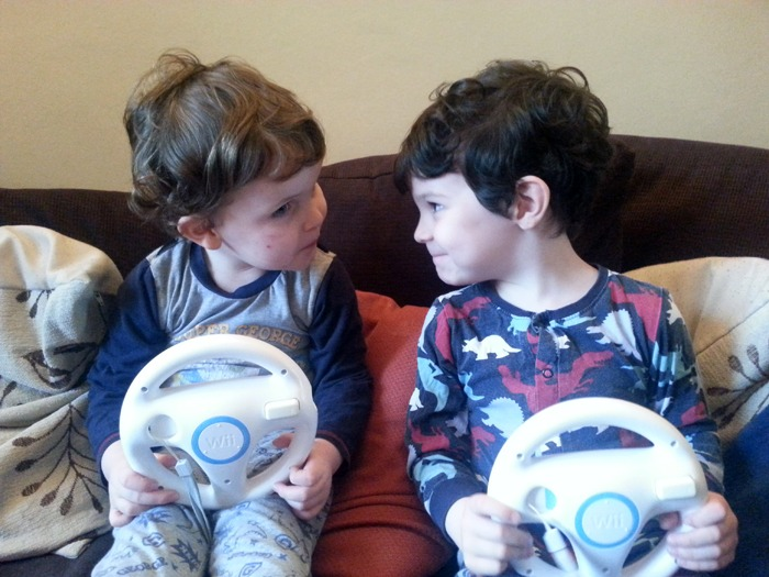 Two little boys playing a video game.