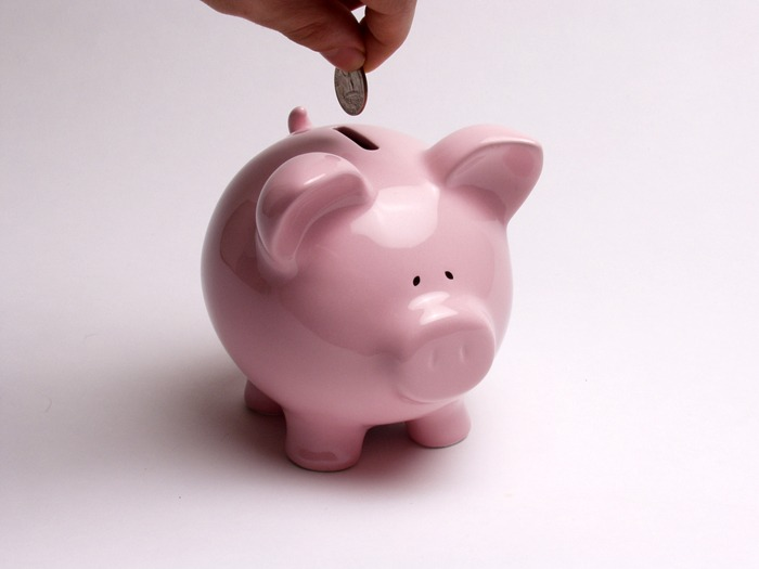 A piggy bank with a coin being put in it.