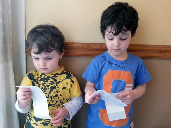 Two young boys looking at shopping receipts.