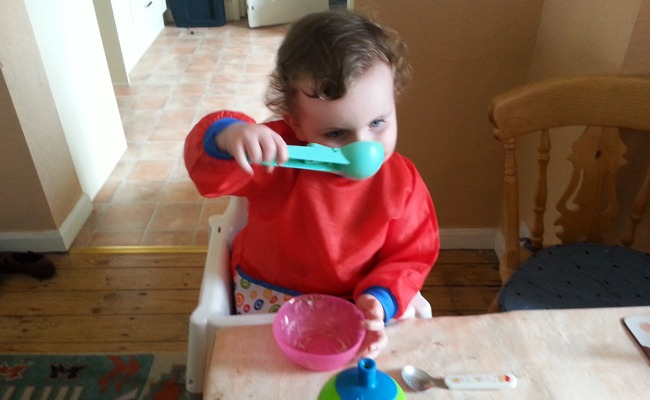 A toddler eating out of an ice cream scoop. His spoon is discarded on the table.