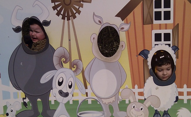 Image of a cartoon farm scene with cut outs for people to put their faces through.