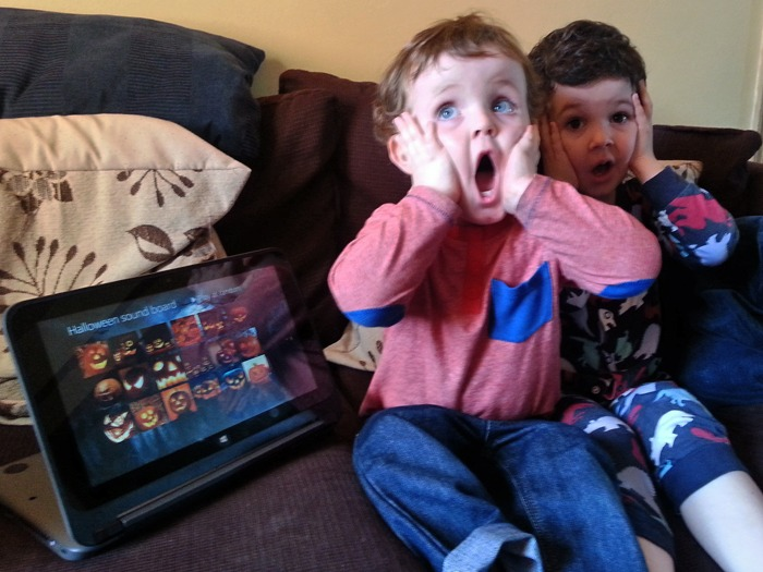 Two young children pretending to be scared by an app on a laptop.