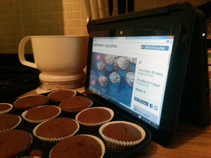 A laptop displaying a recipe with a tray of cakes in front of it.