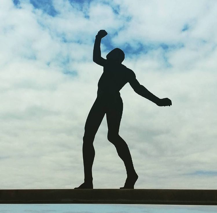 A statue of a tightrope walker in front of a blue sky with white clouds.