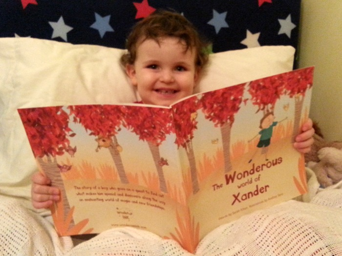 A happy little boy holding his new book.