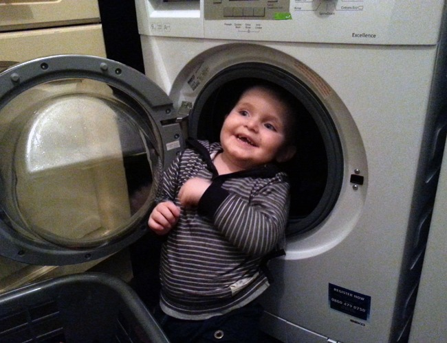 A toddler trying to hide in a washing machine.