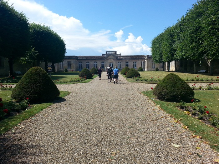 Image of a group of people walking through a grand-looking garden.