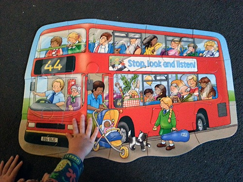 A child putting together the Orchard Toys big bus jigsaw puzzle.