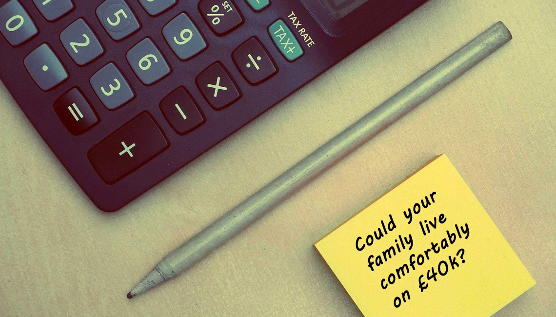 "A calculator, pen and note reading: ""Could your family live comfortably on £40k?"""