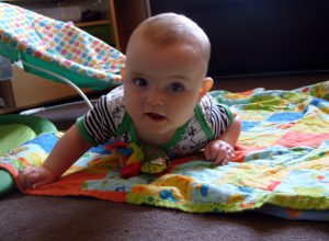A baby boy trying to crawl.