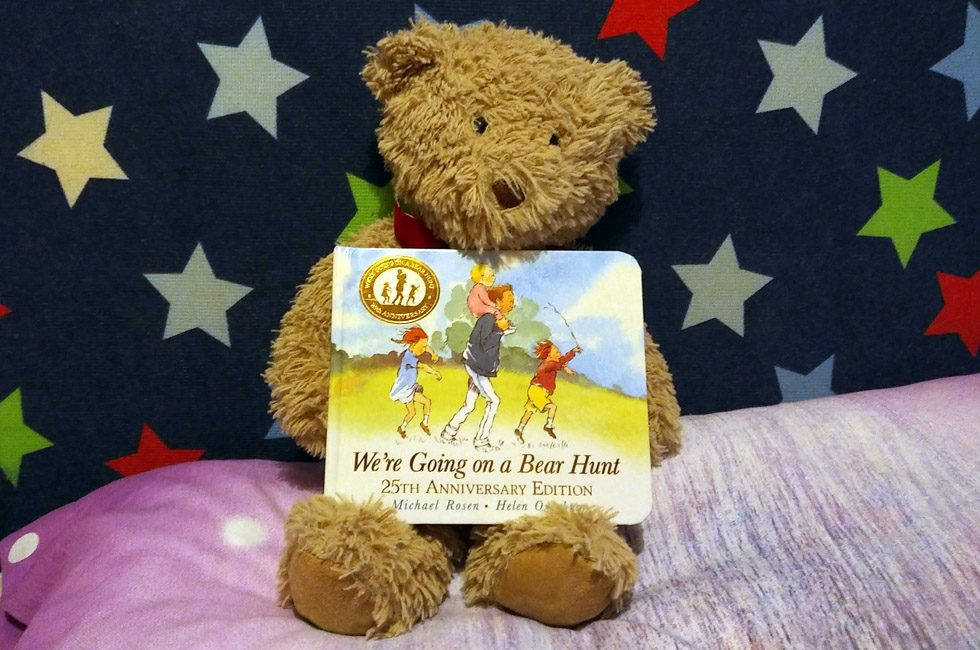 A teddy bear with a copy of We're Going on a Bear Hunt.