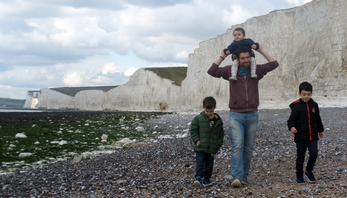 A father and his three children on the beach at Birling Gap.