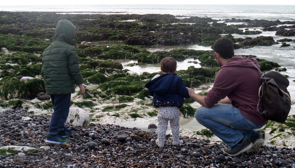 A father and two children looking at rockpools.