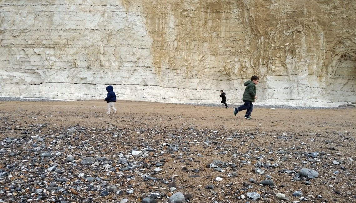 Three children running around on Birling Gap beach.