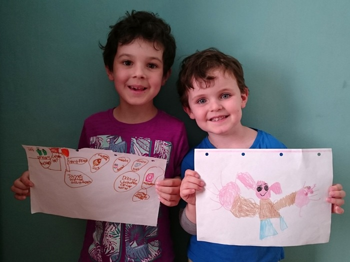 Two boys happily showing the drawings they have done of Roald Dahl characters.