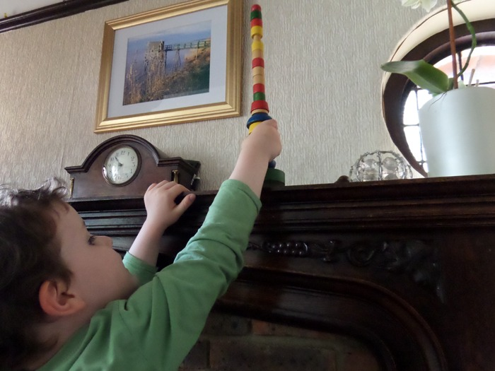 A young boy reaching for an item on a shelf during a scavenger hunt.