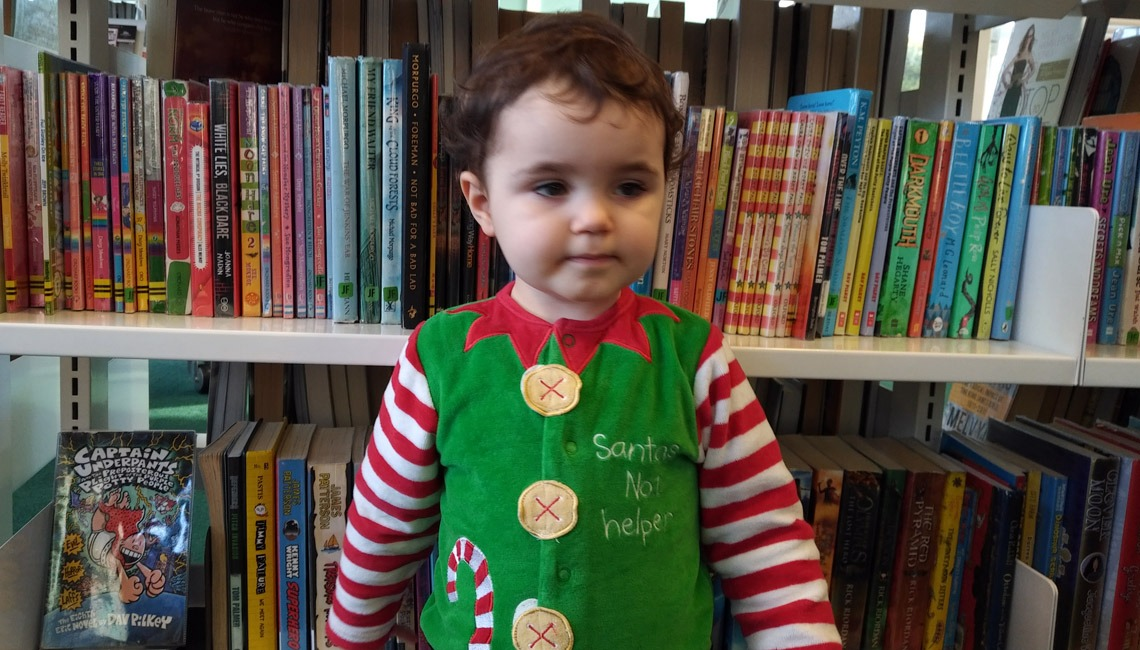 A toddler dressed as an elf in a library and looking a little worse for wear.