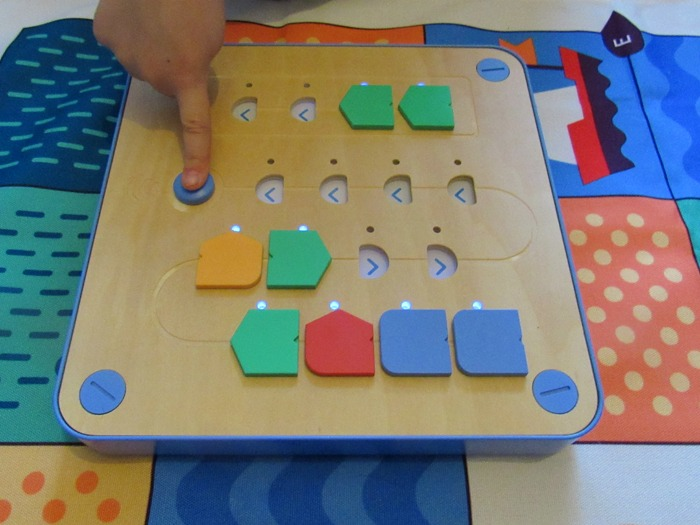 A child pressing a button on Cubetto's board.