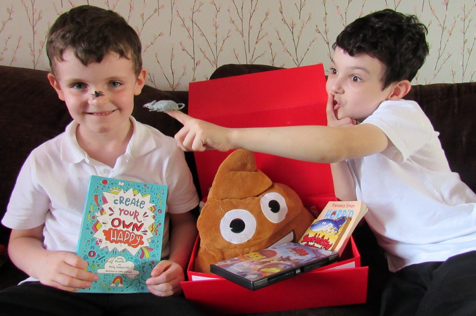Two boys with a copy of Create Your Own Happy and a laughter kit.