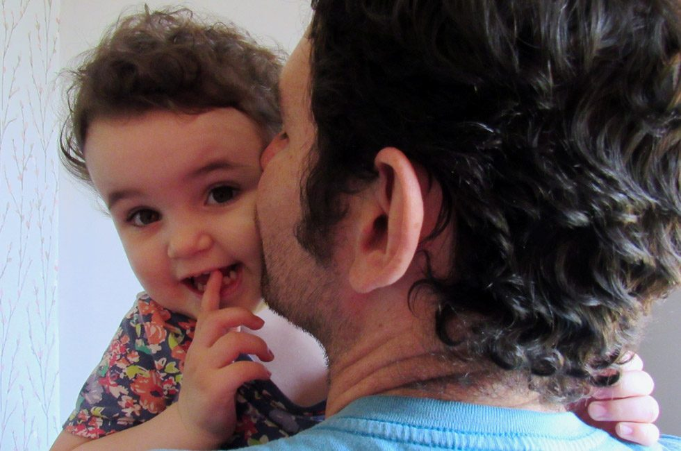 A father cuddling his two-year-old daughter.
