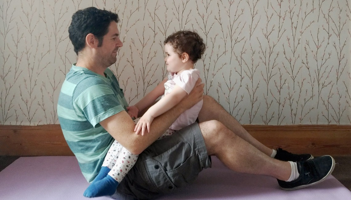 A father doing exercises by using his toddler daughter as a weight.