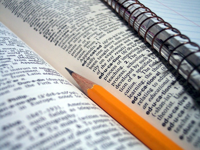 A dictionary with a pencil and writing pad.
