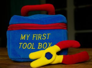 A toy tool box and toy pliers.