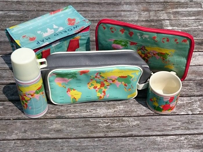 A flask, wash bag, cool bag, mug and tablet cover all with a retro world map design.