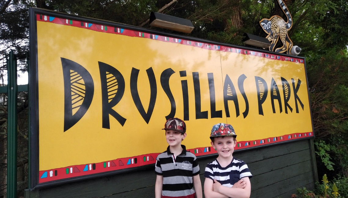 Two young boys in front of the Drusillas Park sign.