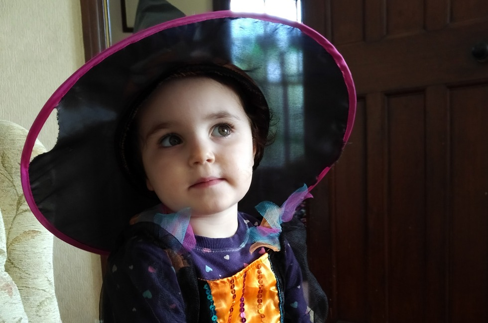 A toddler dressed as a witch. Though she be but little, she is fierce!