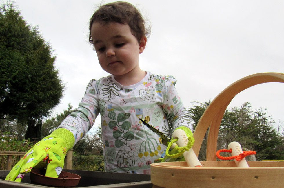 A toddler planting seeds in pots.