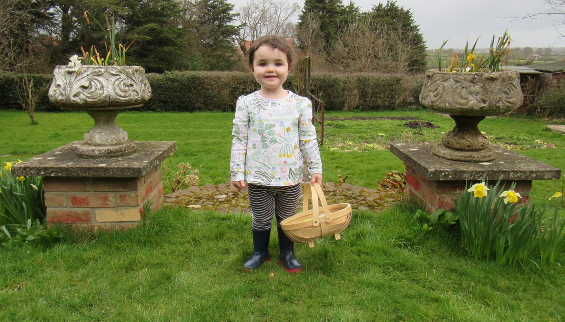 A toddler holding a trug containing gardening tools.