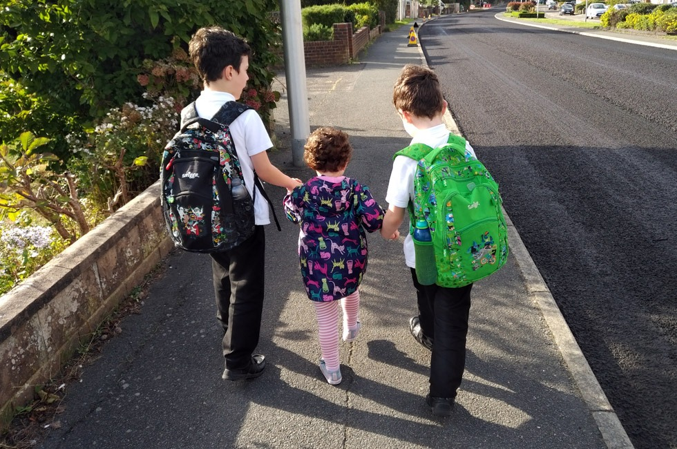 Three siblings walking home from school together.