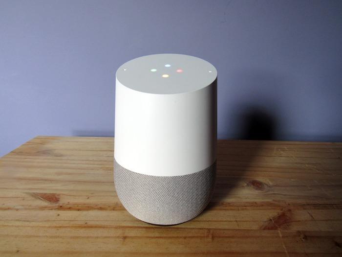 A Google Home smart speaker with its lights on.