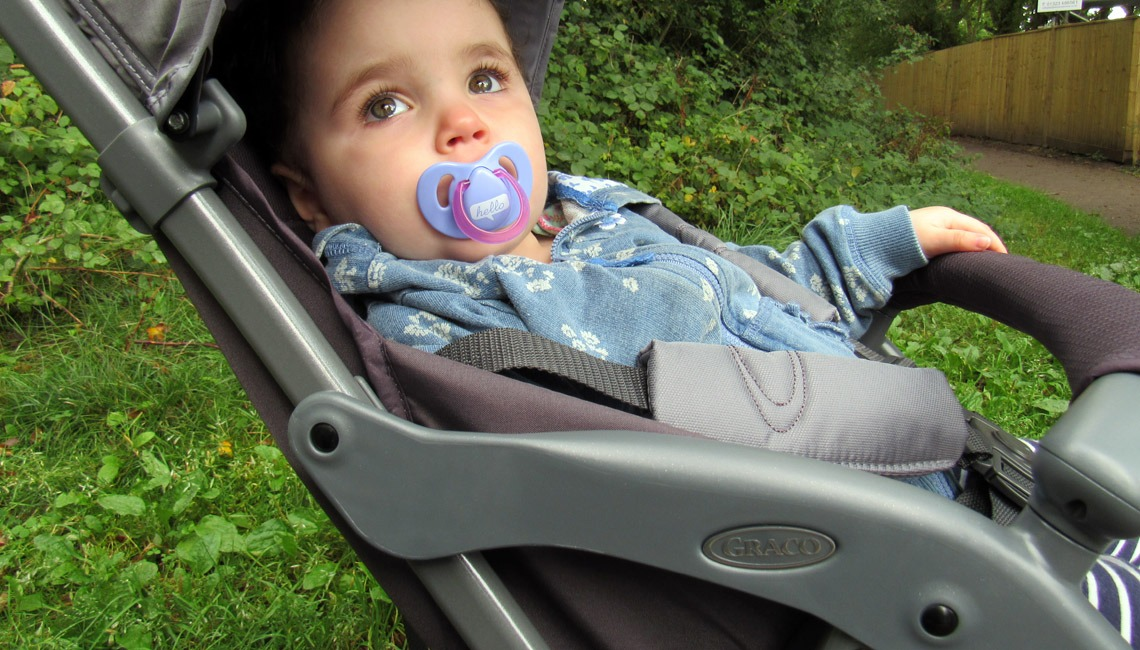 A toddler sitting in the Graco Featherweight stroller.