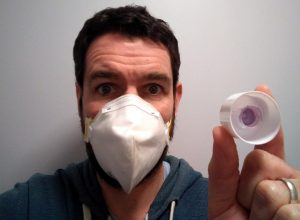 A man wearing a surgeon-style mask holding a dirty toothpaste lid.