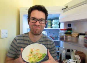 A man pulling a face with a bowl of salad.