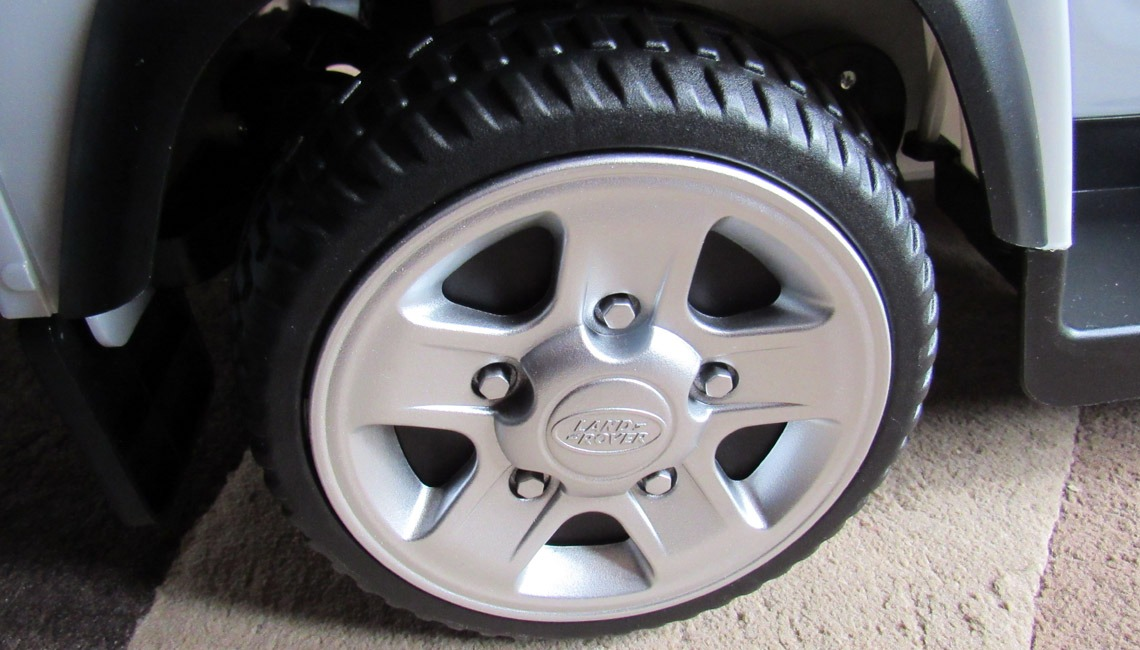 The wheel of a Land Rover Defender Ride On.